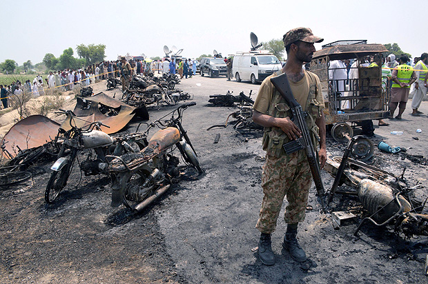 A soldier stands guard amid burnt out cars and motorcycles at the scene of an oil tanker explosion in Bahawalpur, Pakistan June 25, 2017. REUTERS/Stringer ORG XMIT: GGG-PAK204