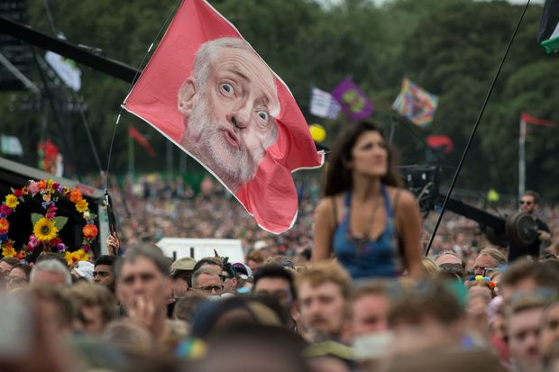 Music fans listen as Jeremy Corbyn, Leader of the Labour Party, addresses the crowd from the Pyramid Stage during the Glastonbury Festival of Music and Performing Arts on Worthy Farm near the village of Pilton in Somerset, southwest England, on June 24, 2017. / AFP PHOTO / OLI SCARFF ORG XMIT: 2265