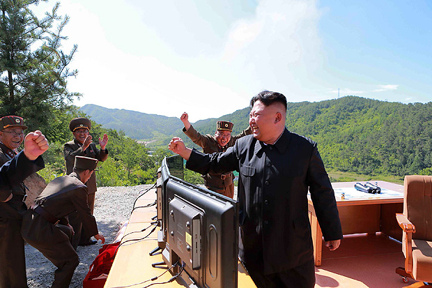 """This picture taken and released on July 4, 2017 by North Korea's official Korean Central News Agency (KCNA) shows North Korean leader Kim Jong-Un (R) reacting after the test-fire of the intercontinental ballistic missile Hwasong-14 at an undisclosed location. North Korea declared on July 4 it had successfully tested its first intercontinental ballistic missile -- a watershed moment in its push to develop a nuclear weapon capable of hitting the mainland United States. / AFP PHOTO / KCNA VIA KNS / STR / South Korea OUT / REPUBLIC OF KOREA OUT ---EDITORS NOTE--- RESTRICTED TO EDITORIAL USE - MANDATORY CREDIT """"AFP PHOTO/KCNA VIA KNS"""" - NO MARKETING NO ADVERTISING CAMPAIGNS - DISTRIBUTED AS A SERVICE TO CLIENTS THIS PICTURE WAS MADE AVAILABLE BY A THIRD PARTY. AFP CAN NOT INDEPENDENTLY VERIFY THE AUTHENTICITY, LOCATION, DATE AND CONTENT OF THIS IMAGE. THIS PHOTO IS DISTRIBUTED EXACTLY AS RECEIVED BY AFP. /"""
