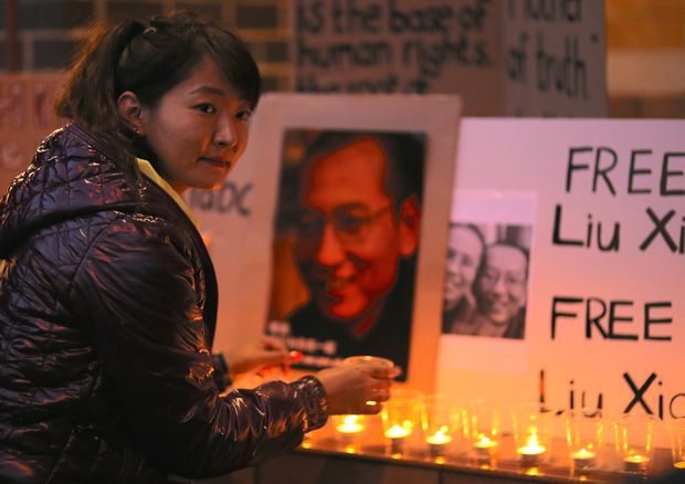 A member of the Australian Tibetan community places a candle near a banner during a candlelight vigil for the Chinese Nobel Peace Prize-winning dissident Liu Xiaobo outside the Chinese consulate in Sydney, Australia, July 12, 2017. REUTERS/Steven Saphore ORG XMIT: DBG352