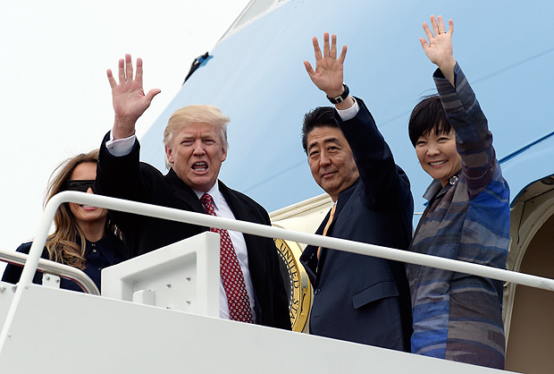 "FILE - This Feb. 10, 2017, file photo shows President Donald Trump and Japanese Prime Minister Shinzo Abe, accompanied by their wives, first lady Melania Trump and Akie Abe, as they wave before boarding Air Force One at Andrews Air Force Base Md. In the world of diplomacy, some things are bound to get lost in translation. President Donald Trump, who sat next to Japan's first lady during dinner at a recent international summit, says Akie Abe can't muster even a ""hello"" in English. In fact, she can handle a basic conversation in English, according to two people who have worked on events with the first lady. That raised questions about whether something was lost in translation or there was an intentional snub. (AP Photo/Susan Walsh, File) ORG XMIT: WX105"