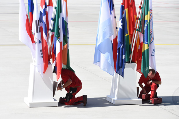 Employees fix flag holders at the airport in Hamburg, northern Germany on July 6, 2017. Leaders of the world's top economies will gather from July 7 to 8, 2017 in Germany for likely the stormiest G20 summit in years, with disagreements ranging from wars to climate change and global trade. / AFP PHOTO / Christof STACHE