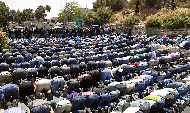 Palestinian Muslim worshippers pray outside Jerusalem's old city on July 28, 2017. Israel barred men under 50 from prayers at the sensitive Jerusalem holy site, with more clashes feared after Palestinians ended a boycott of the compound and entered for the first time in two weeks. / AFP PHOTO / Jack GUEZ
