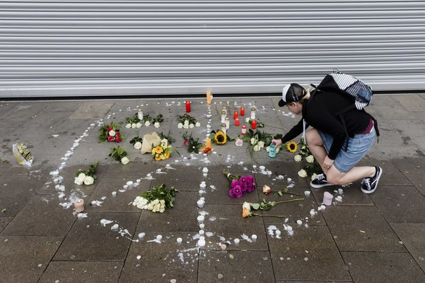 A woman places flowers near a supermarket in Hamburg, Germany, Saturday, July 29, 2017. A man armed with a kitchen knife fatally stabbed one person at athe supermarket Friday in the northern German city of Hamburg and six others were injured as he fled, police said. He was overpowered and arrested. (Markus Scholz/dpa via AP) ORG XMIT: XHBG105