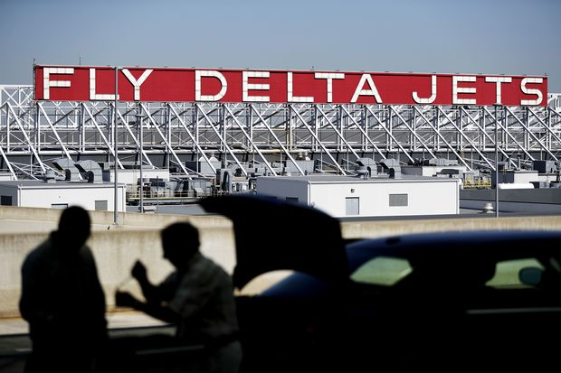 FILE - In this Thursday, Oct. 13, 2016, file photo, a Delta Air Lines sign overlooks the unloading area at Hartsfield-Jackson Atlanta International Airport, in Atlanta. On Tuesday, July 25, 2017, Delta Air Lines apologized after an argument between a pilot and a flight attendant delayed a Delta Connection flight on Monday from New York's LaGuardia Airport to Portland, Maine. The flight was operated by Delta subsidiary Endeavor Air. (AP Photo/David Goldman, File) ORG XMIT: NYBZ246