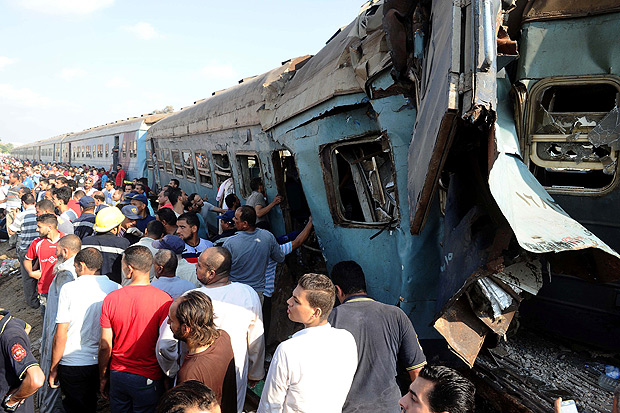 People gather at the site of a train collision in the area of Khorshid, in Egypts Mediterranean city of Alexandria, on August 11, 2017. At least 36 people were killed as two trains collided outside of Alexandria, in one of the deadliest in a string of such accidents in Egypt, the health ministry said. / AFP PHOTO