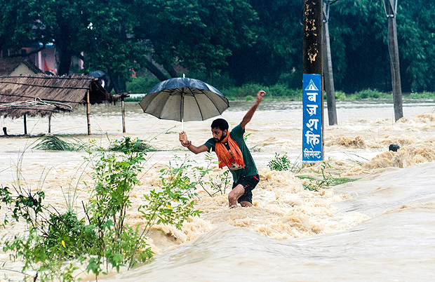 A Nepalese man looses his balance while crossing a flooded street in Birgunj, Nepal, Sunday, Aug. 13, 2017. An official said torrential rain, landslides and flooding have killed dozens of people in Nepal over the past three days, washing away hundreds of homes and damaging roads and bridges across the Himalayan country. (AP Photo/Manish Paudel) ORG XMIT: DEL110