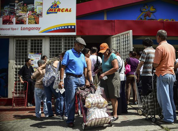 A man pulls a mobile travel cart loaded with bags of foodstuff, as he leaves one of the food distribution centers called CLAP (Local Committees for Supply and Production), which are run by community leaders, in Caracas on August 16, 2017.