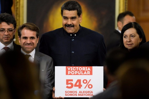 "Venezuelan President Nicolas Maduro (C) holds a sign that reads ""popular victory 54 percent; we are happiness, we are the majority"" after a press conference with international media correspondents at the Miraflores Presidential Palace in Caracas on October 17, 2017. / AFP PHOTO / FEDERICO PARRA ORG XMIT: FPZ4212"