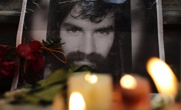 A photo of missing activist Santiago Maldonado is surrounded by candles at a makeshift memorial outside the morgue in Buenos Aires, Argentina, Saturday, Oct. 21, 2017. Sergio Maldonado, the brother of the Argentine protester whose disappearance prompted large demonstrations, says the family believes that a body found this week in a Patagonia river is that of Santiago Maldonado. (AP Photo/Natacha Pisarenko) ORG XMIT: XNP101