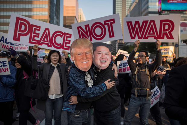 TOPSHOT - Demostrators dressed as North Korean leader Kim Jong-Un (R) and US President Donald Trump (L) embrace during a peace rally in Seoul on November 5, 2017. Thousands of South Koreans called for peace in a protest against an upcoming visit by Donald Trump as he begins a two-week Asia tour amid tension over North Korea's weapons drive. / AFP PHOTO / Ed JONES