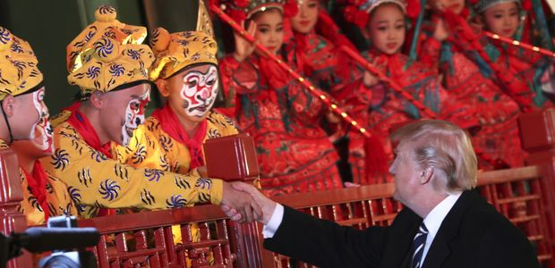 President Donald Trump, center, shakes hands with an opera performer, accompanied by Chinese President Xi Jinping, as they tour opera performance at the Forbidden City, Wednesday, Nov. 8, 2017, in Beijing, China. Trump is on a five country trip through Asia traveling to Japan, South Korea, China, Vietnam and the Philippines. (AP Photo/Andrew Harnik) ORG XMIT: TKSK355