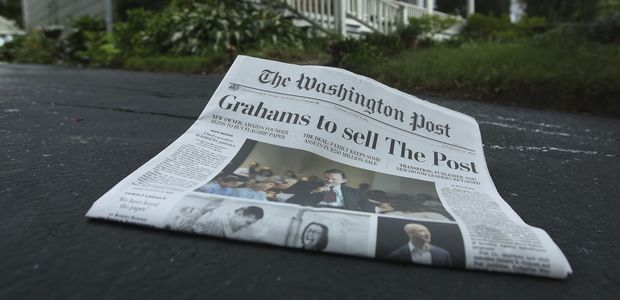 A morning edition of the Washington Post lies in a driveway after delivery in this photo illustration taken in Silver Spring, Maryland August 6, 2013. Amazon.com Inc founder Jeff Bezos will buy the Washington Post newspaper for $250 million in a surprise deal that ends the Graham family's 80 years of ownership and hands one of the country's most influential publications to the businessman whose Internet company has transformed retailing. Donald Graham, the chairman and CEO of the Washington Post Co, said in an interview that he and his niece Katharine Weymouth, the Post's publisher, made the decision to put the newspaper up for sale earlier this year after looking at its financial forecasts. REUTERS/Gary Cameron (UNITED STATES - Tags: BUSINESS MEDIA) ORG XMIT: GAC01