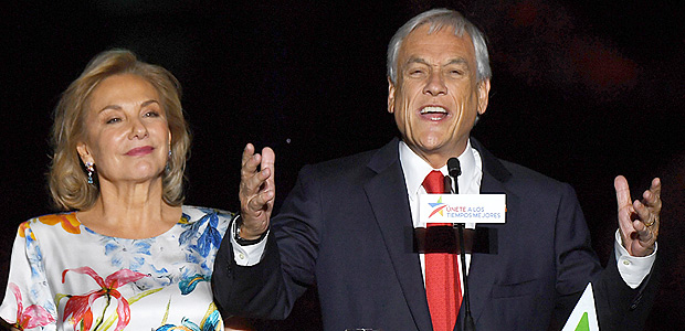 Chilean presidential candidate Sebastian Pinera (R), next to his wife Cecilia Morel, publicly celebrates his victory in Santiago after the runoff election on December 17, 2017. Conservative billionaire Sebastian Pinera will return as Chile's president, the election results show. His rival, leftist challenger Alejandro Guillier, a TV presenter turned senator who ran as an independent but was backed by outgoing center-left President Michelle Bachelet, recognized his defeat. / AFP PHOTO / Martin BERNETTI