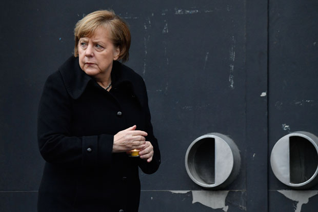 German Chancellor Angela Merkel holds a candle as she attends the inauguration of the memorial for the victims of the 2016 deadly truck attack at the Christmas market in front of the Kaiser-Wilhelm-Gedaechtniskirche (Kaiser Wilhelm Memorial Church) at Breitscheidplatz in Berlin, on December 19, 2017. Germany commemorates the victims of the devastating Christmas market attack from December 19, 2016 that claimed 12 lives and wounded 70, with a memorial bearing a 14-metre-long (46-foot) golden crack in the grounds engraved with the victims' names. / AFP PHOTO / John MACDOUGALL