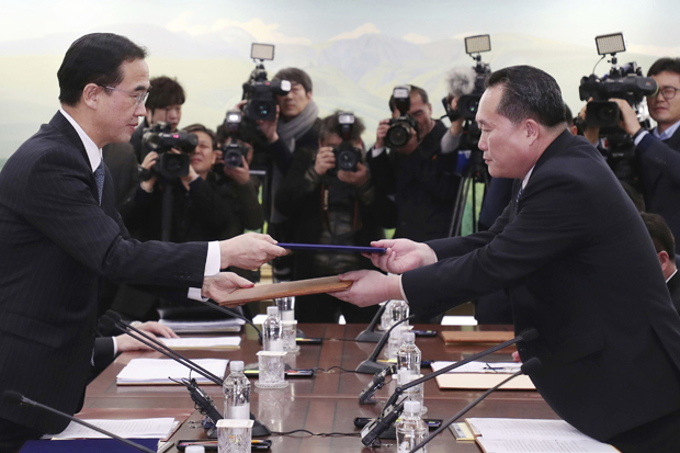 The head of North Korean delegation Ri Son Gwon, right, exchanges documents with South Korean Unification Minister Cho Myoung-gyon after their meeting at Panmunjom in the Demilitarized Zone in Paju, South Korea, Tuesday, Jan. 9, 2018. The rival Koreas took steps toward reducing their bitter animosity during rare talks Tuesday, as North Korea agreed to send a delegation to next month's Winter Olympics in South Korea and reopen a military hotline. (Korea Pool/Yonhap via AP) ORG XMIT: XAHN816