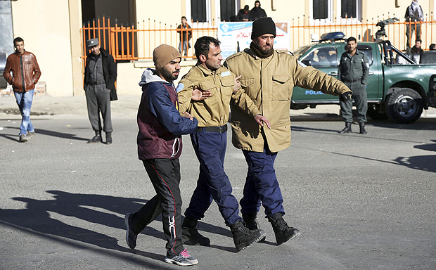 Afghan security personnel escort a man rescued from the Intercontinental Hotel after an attack in Kabul, Afghanistan, Sunday, Jan. 21, 2018. Gunmen stormed the hotel and sett off a 12-hour gun battle with security forces that continued into Sunday morning, as frantic guests tried to escape from fourth and fifth-floor windows. (AP Photo/Rahmat Gul) ORG XMIT: XRG106