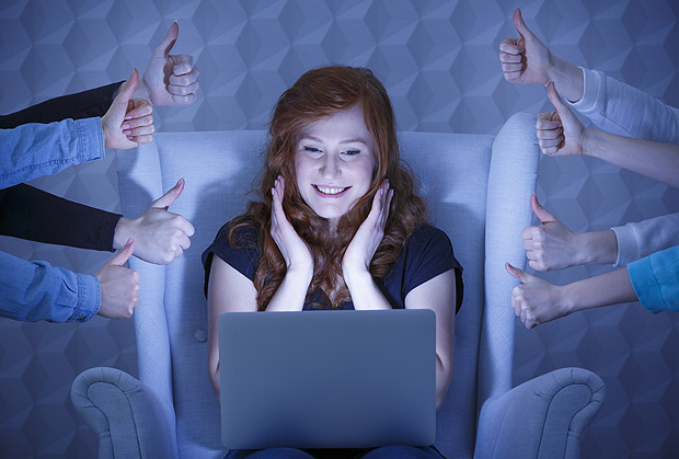 Happy girl having positive comments of her social media profile