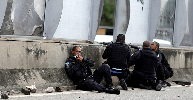 Policemen take up positions during an operation against drug dealers near the Mare slum complex in Rio de Janeiro
