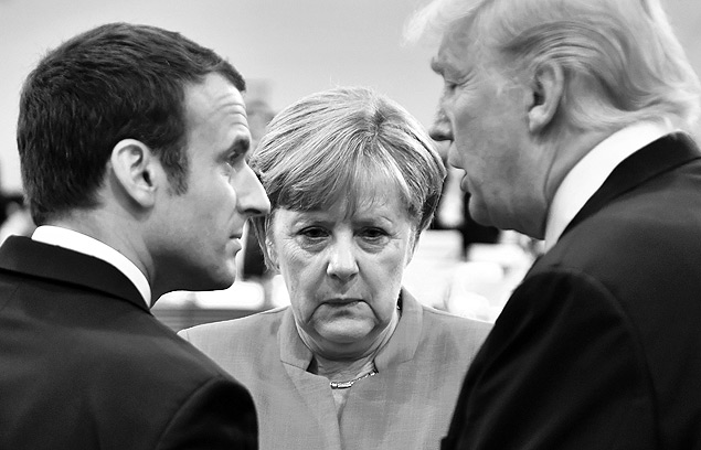 TOPSHOT - (L-R) French President Emmanuel Macron, German Chancellor Angela Merkel and US President Donald Trump confer at the start of the first working session of the G20 meeting in Hamburg, northern Germany, on July 7. Leaders of the world's top economies will gather from July 7 to 8, 2017 in Germany for likely the stormiest G20 summit in years, with disagreements ranging from wars to climate change and global trade. / AFP PHOTO / AFP PHOTO AND POOL / John MACDOUGALL
