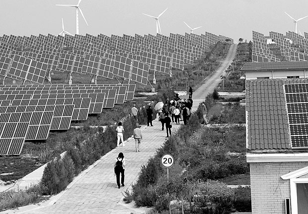Painéis de energia solar em Taiyangshan, na China. *** This photo taken on September 22, 2011 shows people visiting the Taiyangshan solar panel field in northern China's Ningxia region. In a new show of anger at China's trade practices, a major US maker of solar cells and panels SolarWorld Industries America, a subsidiary of Germany-based SolarWorld AG, announced on October 19, 2011 it was filing a formal complaint targeting Beijing, as US lawmakers who blame China's rise for lost American jobs have stepped up calls for Washington to confront Beijing. AFP PHOTO / LILIAN WU