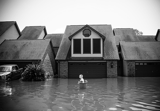 TOPSHOT - Jenna Fountain carries a bucket down Regency Drive to try to recover items from their flooded home in Port Arthur, Texas, September 1, 2017. Storm-weary residents of Houston and other Texas cities began returning home to assess flood damage from Hurricane Harvey but officials warned the danger was far from over in parts of the battered state. / AFP PHOTO / [Assignment # goes here] / Emily Kask