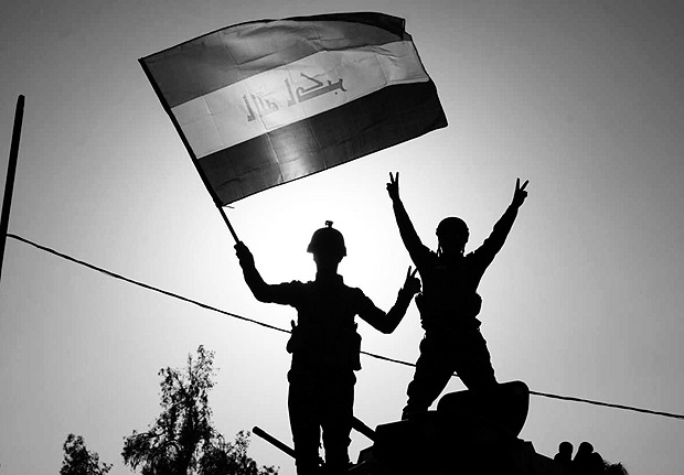 """Iraq's federal police members wave Iraq's national flag as they celebrate in the Old City of Mosul on July 9, 2017 after the government's announcement of the """"liberation"""" of the embattled city. Iraq declared victory against the Islamic State group in Mosul on July 9 after a gruelling months-long campaign, dealing the biggest defeat yet to the jihadist group. / AFP PHOTO / FADEL SENNA ORG XMIT: 2193"""