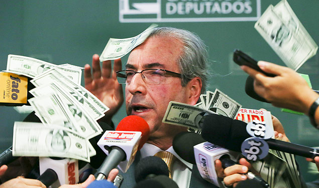 Eduardo Cunha stands by fake dollar notes with his effigy thrown by protesters during an interview at the National Congress