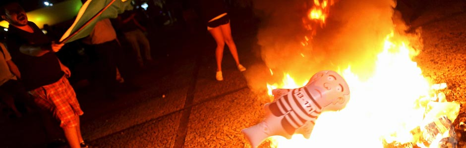 "A demonstrator throws an inflatable doll known as ""Pixuleco"" of Brazil's former president Luiz Inacio Lula da Silva in a bonfire during a protest at the appointment of Lula da Silva as a minister, in front of the national congress in Brasilia, Brazil, March 16, 2016. REUTERS/Adriano Machado ORG XMIT: BSB126"