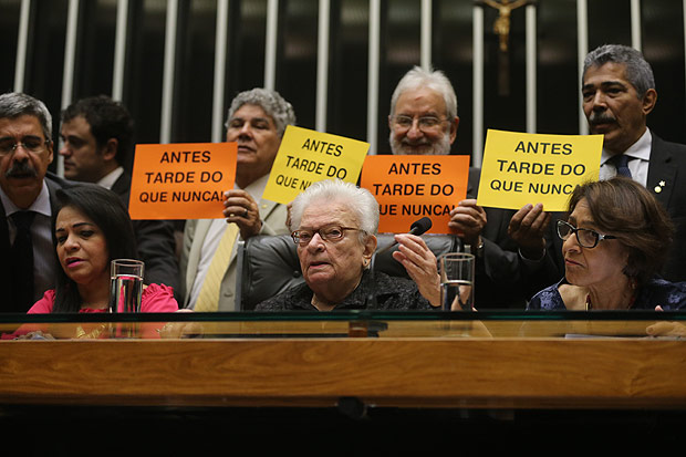 Members of the lower house of Congress hold signs in protest against the speaker Eduardo Cunha, in Brasilia
