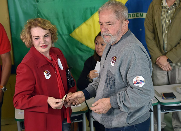 Brazilian former president Luiz Inacio Lula da Silva (R), of the Workers' Party (PT), is pictured with his wife Marisa Leticia at a polling station during the municipal elections' first round at a school in Sao Bernardo do Campo, 25 km south of Sao Paulo, Brazil, on October 2, 2016. Brazilians furious at recession and corruption voted Sunday in municipal elections amid heightened security after a series of murders of candidates. Among the first to cast his ballot in the financial capital Sao Paulo was Brazilian President Michel Temer from the center-left PMDB party, who took over the presidency in August after turning on his former leftist ally Dilma Rousseff and helping to force her from the top job in an impeachment vote. / AFP PHOTO / NELSON ALMEIDA