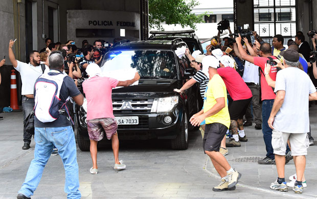 Protesters rush towards the police car that took former governor of Rio Sergio Cabral Filho to the penitentiary Bangu 8, where he will be held on fraud charges, in Rio de Janeiro on November 17, 2016. / AFP PHOTO / TASSO MARCELO ORG XMIT: TAS1151