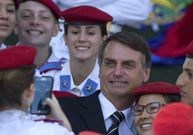 Brazilian congressman Jair Bolsonaro poses for photos with soldiers and cadets during a a ceremony commemorating Army Day, in Brasilia, Brazil, Wednesday, April 19, 2017. Bolsonaro, a potential presidential candidate for Brazil's 2018 election, is backed by the military and some conservative sectors. (AP Photo/Eraldo Peres) ORG XMIT: ERA110