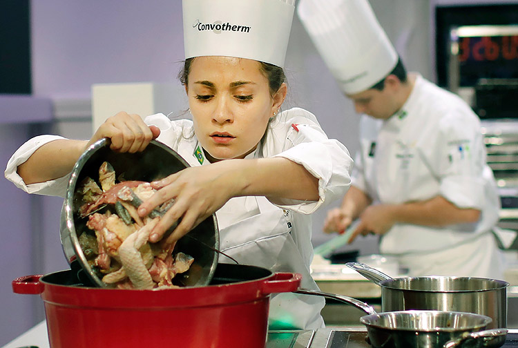 """Giovanna Grossi, of Brazil, prepares food during the """"Bocuse d'Or"""" trophy, in Lyon, central France, Wednesday, Jan. 25, 2017. The contest, a sort of world cup of cuisine, was started in 1987 by Lyon chef Paul Bocuse to reward young international culinary talents. (AP Photo/Laurent Cipriani) ORG XMIT: CIP113"""