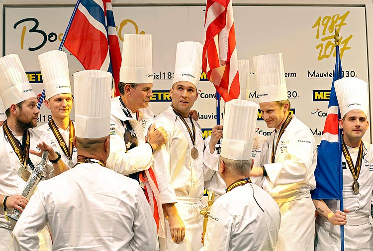 """Mathew Peters of USA, center, celebrates on the podium with his teammates after winning the """"Bocuse d'Or"""" (Golden Bocuse) trophy, with Christopher William Davidsen of Norway, far left, who finished second, and third placed Viktor Andresson of Iceland, far right, in Lyon, central France, Wednesday, Jan. 25, 2017. The contest, a sort of world cup of the cuisine, was started in 1987 by Lyon chef Paul Bocuse to reward young international culinary talents. (AP Photo/Laurent Cipriani) ORG XMIT: CIP119"""