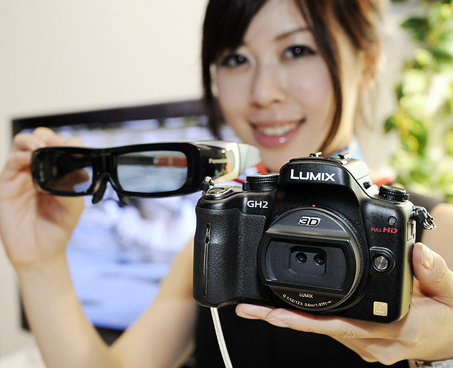 "A model displays Japanese electronics maker new Panasonic digital single-lens-reflex (SLR) camera ""Lumix GH-2"" with 3D interchangable lenses, which can record 3D images and play on the 3D televisions at home, during a preview at Ceatec, Asia's largest electronics trade show in Chiba, suburban Tokyo on October 5, 2010. Panasonic will put the new camera on the market at the end of this month. AFP PHOTO / Yoshikazu TSUNO"