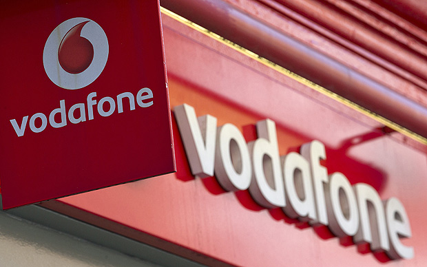 (FILES) A file picture taken in London on September 4, 2013, shows the Vodafone logo. Vodafone's annual profit rocketed to £59.3 billion, boosted by the sale of a stake in US joint-venture Verizon Wireless and despite more problems in Europe, the British mobile phone giant said on Tuesday May 20, 2014. AFP PHOTO / JUSTIN TALLIS/FILES ORG XMIT: JR066