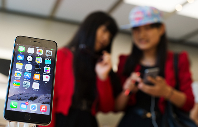 Chinese girls check out the iPhone 6 in an Apple store in Shanghai on October 17, 2014. Apple began selling its latest iPhone in China, nearly a month after other major territories due to a licence delay by regulators, but it faces a tough battle with rivals led by Samsung in the crucial market. Staff at an Apple Store in downtown Shanghai clapped and congratulated iPhone 6 customers as they left the shop, which opened two hours early for those who had pre-ordered. AFP PHOTO / JOHANNES