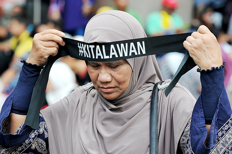 """A supporter of Malaysia's opposition leader Anwar Ibrahim wears a headband with a hashtag that translates to """"we will fight"""" during a protest demanding his release in Kuala Lumpur on March 28, 2015. Malaysian police arrested three leading opposition politicians in a bid to thwart a protest march on March 28 demanding the release of jailed opposition leader Anwar Ibrahim, his party said. AFP PHOTO / MOHD RASFAN ORG XMIT: MRN047"""