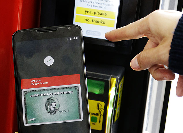 A Google employee gives a demonstration of Android Pay on a phone at Google I/O 2015 in San Francisco, Thursday, May 28, 2015. Google's next version of its Android operating system will boast new ways to fetch information, pay merchants and protect privacy on mobile devices as the Internet company duels with Apple in the quest to make their technology indispensable. (AP Photo/Jeff Chiu) ORG XMIT: CAJC118