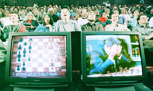 Xadrez: duelo entre Garry Kasparov e o computador Deep Blue da I.B.M: World chess champion Garry Kasparov rests his head in his hands as he is seen on a monitor during game six of the chess match against IBM supercomputer Deep Blue, May 11. The supercomputer made chess history Sunday when it defeated Kasparov for an overall victory in their six game re-match, the first time a computer has triumphed over a reigning world champion in a classical match. Kasparov resigned after 19 moves. ms/Photo by Peter Morgan REUTERS*** NÃO UTILIZAR SEM ANTES CHECAR CRÉDITO E LEGENDA***