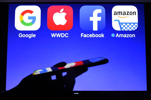This photograph taken on September 28, 2017, shows a smartphone being operated in front of GAFA logos (acronym for Google, Apple, Facebook and Amazon web giants) as background in Hédé-Bazouges, western France. / AFP PHOTO / Damien MEYER