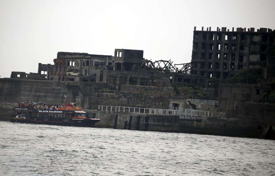 "In this June 29, 2015 photo, a tourist boat arrives at Hashima Island, commonly known as Gunkanjima, which means ""Battleship Island,"" off Nagasaki, Nagasaki Prefecture, southern Japan. The island is one of 23 old industrial facilities seeking UNESCO's recognition as world heritage ""Sites of Japan's Meiji Industrial Revolution"" meant to illustrate Japan's rapid transformation from a feudal farming society into an industrial power at the end of the 19th century. UNESCO's World Heritage Committee is expected to approve the proposal during a meeting being held in Bonn, Germany, through July 9. (AP Photo/Eugene Hoshiko) ORG XMIT: XEH412"