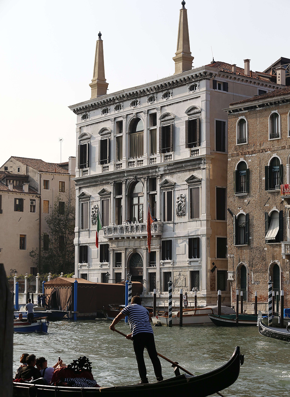 """A general view shows a gondola on the Grand canal near the Aman hotel (L) where US actor George Clooney and British fiancee, Amal Alamuddin will celebrate their wedding party on September 27, 2014 in Venice. George Clooney has said goodbye to bachelorhood in Venice with a stag party at his favourite restaurant with Hollywood chums, and was gearing up for a day of glamourous pre-wedding celebrations. The actor had swept into the floating city yesterday with his British fiancee Amal Alamuddin on a watertaxi dubbed """"Amore"""", zipping up the Grand Canal to cheers from fans at the start of nuptials set to draw out over the weekend. AFP PHOTO / PIERRE TEYSSOT ORG XMIT: ITA3515"""