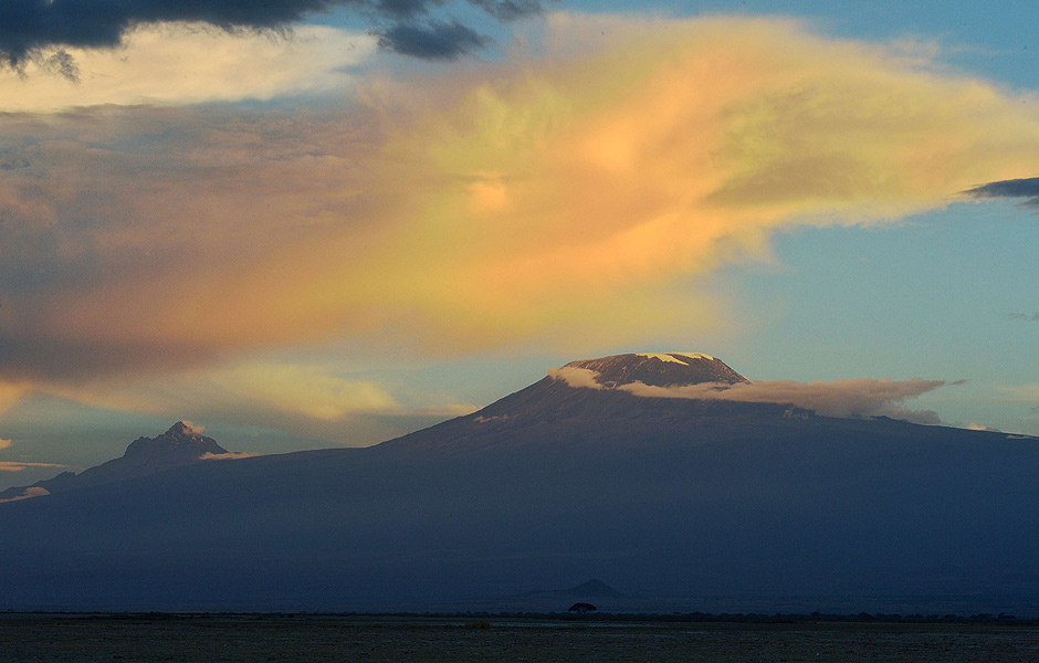 Africa's highest mountain, Kilimanjaro stands in the dying light of dusk over the rolling plains of the Amboseli national reserve November 13, 2015. The first delegation of the China-Africa Wildlife Ambassadors (CAWA) drawn from some of China's media corporations including JC Decaux China, iFENG.com, Beijing MTR Corporation, Shenzhen Press Group, Fulong Media and DEEP magazine arrived in Kenya as part of China's strategy to use iconic members of society to speak up against ivory trade and mobilizing society to stigmatize ivory consumption. In September this year, Chinese president Xi Jinping announced that China will take significant and timely steps to halt the domestic commercial trade of ivory thought to spur, on average, a killing of an elephant every 15 minutes for its ivory accirding to the International Fund for Animal Welfare (IFAW). AFP PHOTO/Tony KARUMBA ORG XMIT: TK25
