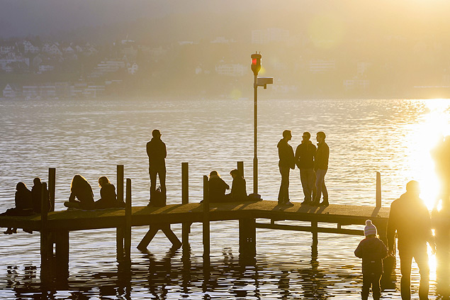 WBR34. Zurich (Switzerland Schweiz Suisse), 27/12/2015.- Strollers stand in the golden light of the sun on the shore of the Lake Zurich in Zurich, Switzerland, 27 December 2015. Wide parts of Europe experience springlike weather and temperatures these days. (Suiza) EFE/EPA/WALTER BIERI ORG XMIT: WBR34