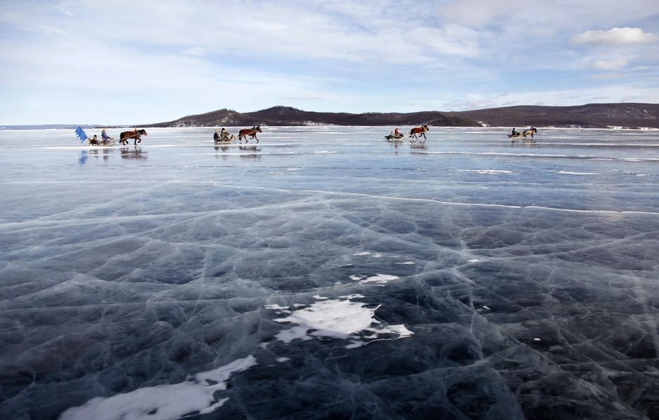 Horses pull sleds during a winter competition as part of the annual two-day Ice Festival on the Khuvsgul Lake March 3, 2015. Picture taken March 3, 2015. REUTERS/B.Rentsendor (MONGOLIA - Tags: TRAVEL ANIMALS SOCIETY) ORG XMIT: PEK50