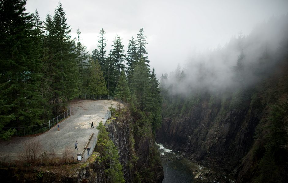 People walk on a lookout above a trail as low cloud hangs over the Capilano River on Christmas Day in North Vancouver, Canada, Friday, Dec. 25, 2015. (Darryl Dyck/The Canadian Press via AP) MANDATORY CREDIT ORG XMIT: VCRD110
