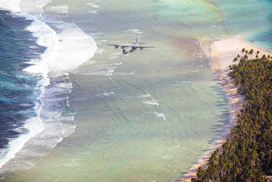 In this Dec. 8, 2015 photo provided by the U.S. Air Force, a Royal Australian Air Force C-130J flies over the Federated States of Micronesia during Operation Christmas Drop. Australian, Japanese and U.S. air force planes are dropping food and toys on remote atolls in the Pacific as part of the U.S. military's longest-running humanitarian relief mission. (Tech. Sgt. Melissa K. Mekpongsatorn/U.S. Air Force via AP) ORG XMIT: HI202