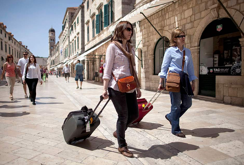 Tourists pull their luggage as they walk on Stradun street in Croatia's UNESCO protected medieval town of Dubrovnik April 29, 2013. The barren Srdj plateau overlooking the mediaeval city of Dubrovnik is a real estate developer's dream, offering breath-taking views of Croatia's top tourist destination. That's precisely why an Israeli-Croatian consortium began planning a billion-euro golf resort there in 2006. Seven years on, construction has yet to start. This project typifies the problems facing foreign investors in Croatia, which joins the European Union on July 1, more than 20 years after it broke away in war from socialist Yugoslavia. Picture taken April 29, 2013. REUTERS/Antonio Bronic (CROATIA - Tags: BUSINESS TRAVEL) ORG XMIT: ABR0168